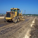 Motorgrader with GPS provides finished subgrade profile and blue topping.